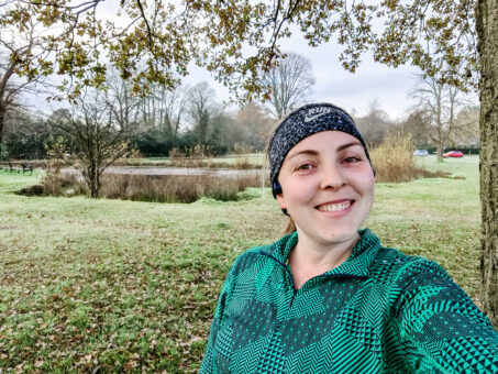 Running selfie in front of green and pond