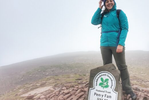 Woman in green coat at top of Pen Y Fan