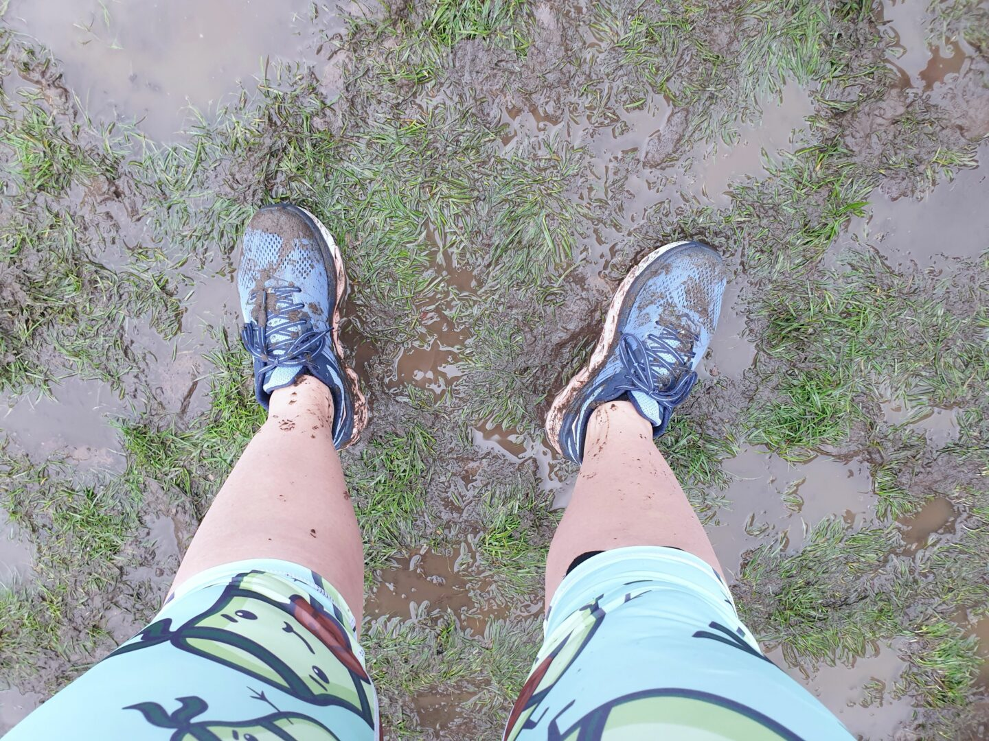 Muddy running shoes in muddy grass field