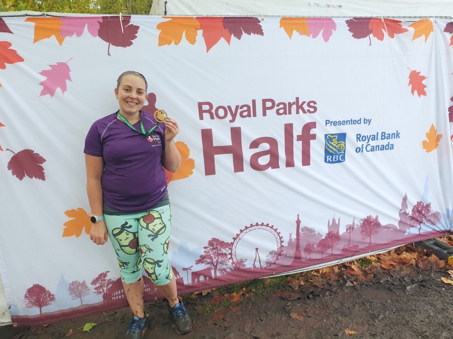 Me in running kit standing in front of Royal Parks Half branding with medal