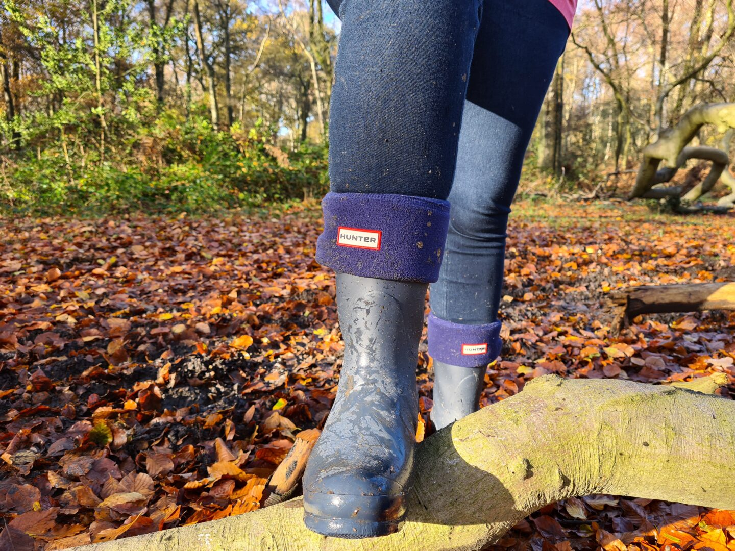 Close up of legs wearing blue Hunter wellies standing in the woods
