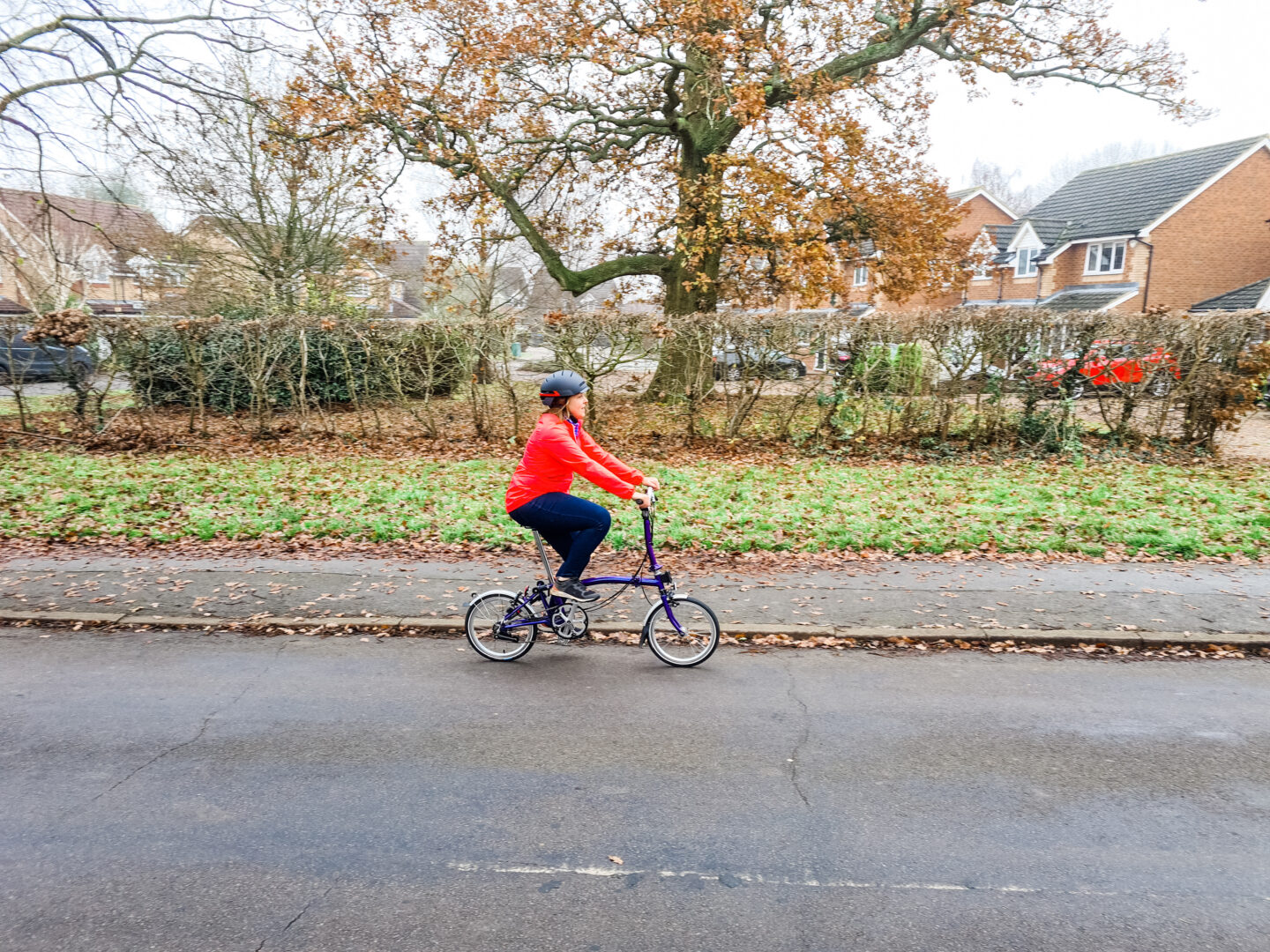 Woman in pink cycling jacket and helmet riding a Brompton bike along the road