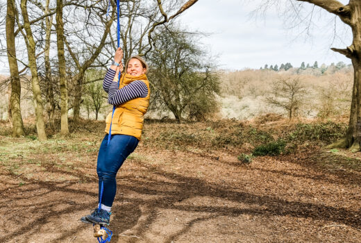 woman in yellow gilet swings on a rope swing smiling in the sunshin