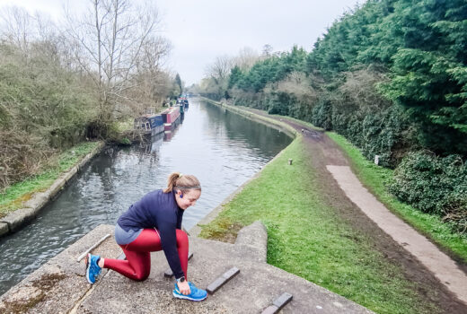 Woman wearing red leggings and black top kneels to tie her shoelaces on canal towpath