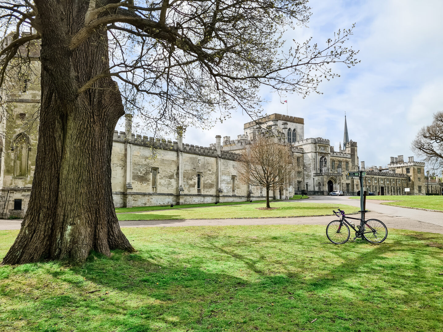 A road bike leans up against a road sign with Ashridge College, an imposing building in the background.