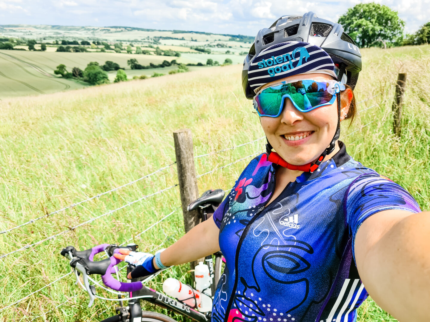 Woman wearing cycling kit smiling at the camera with her hand on a road bike, with a countryside view in the background