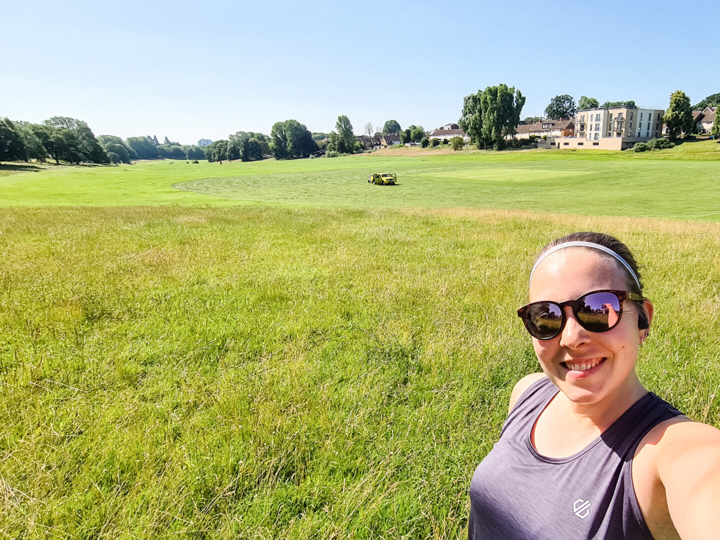 Selfie of woman in grey running vest and sunglasses, with green field behind her