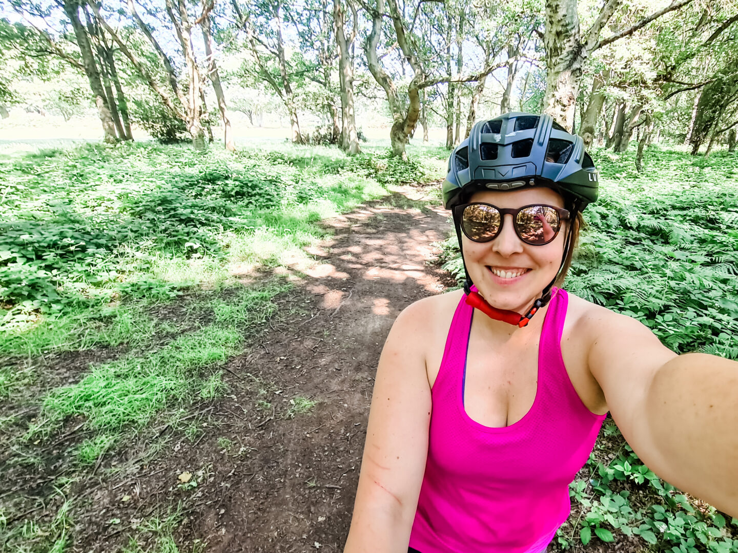A woman in cycling kit smiles at the camera with a wood behind her, a muddy trail disappearing into the distance.